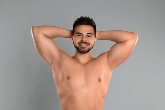Young man showing hairless armpits after epilation procedure on grey background
