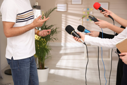 Group of journalists interviewing man in room, closeup