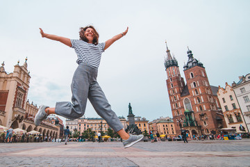 city tourism concept woman jumping at krakow market square saint mary church on background