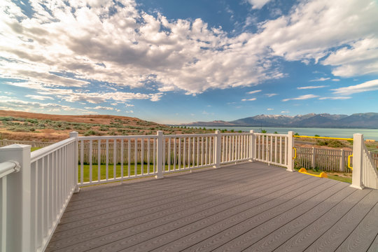 Back porch of a home with view of lake and mountain under cloudy blue sky