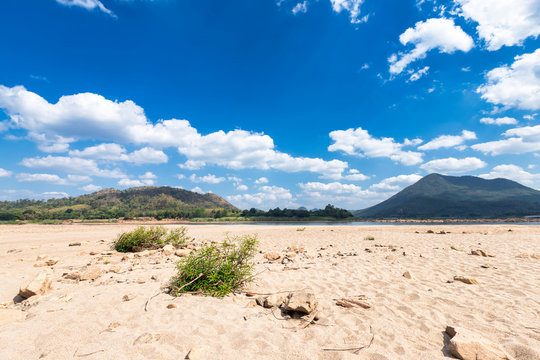 dry sand ground of Mae Khong river with Mountain views on blue sky background texture with white cloud of Laos at the Kaeng Khud Khu rapids at Chiang Khan in Loei province,Thailand,The River Crisis