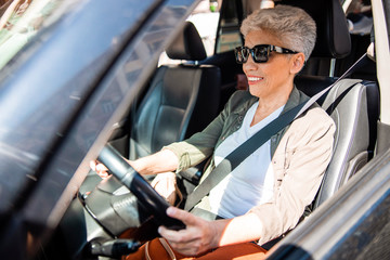 Smiling senior lady in sunglasses sitting in auto