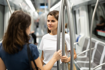 Girlfriends enjoying conversation in subway train