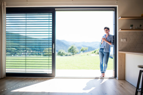 Front view of young woman with coffee standing by patio door at home.