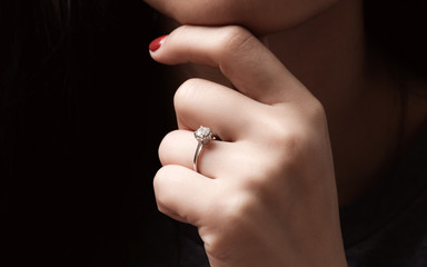 Close up of an elegant engagement diamond ring on woman finger