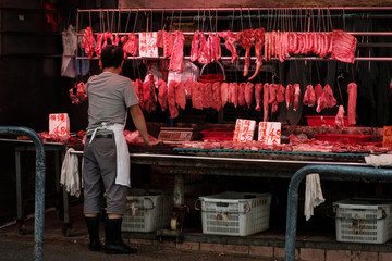 Butcher selling meat on street market store in Hong Kong