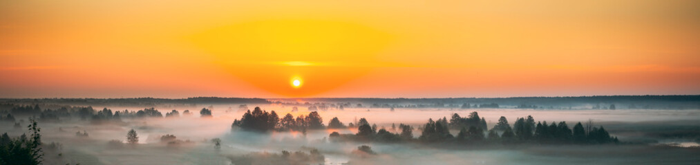 Foto op Aluminium Oost Europa Amazing Sunrise Sunset Over Misty Landscape. Scenic View Of Foggy Morning Sky With Rising Sun Above Misty Forest And River. Early Summer Nature Of Eastern Europe. Panorama