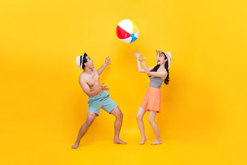 Happy fun Asian couple playing beach ball together