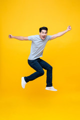 Energetic excited young Asian man in casual clothes jumping in yellow background