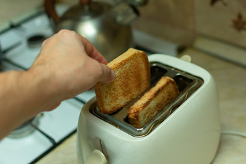 making breakfast toast bread with toaster at home kitchen