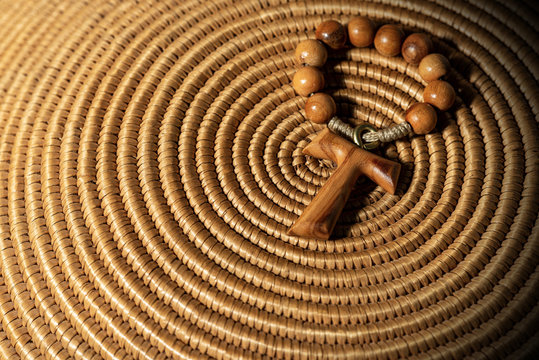 Tau, wooden cross in shape of the letter t (religious symbol of St. Francis of Assisi) with rosary bead, on brown woven wicker texture