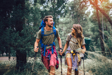 Keuken foto achterwand Olijf Smiling couple walking with backpacks over natural background