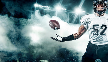 American football player. Sportsman with ball in helmet on stadium in action. Sport wallpaper. Team...