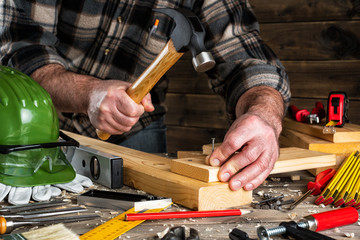 Close-up. Carpenter with hammer and nails fixes a wooden board. Construction industry, do it yourself. Wooden work table.