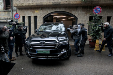 Journalists take pictures of a car leaving the garage of a house believed to belong to former Nissan chairman Carlos Ghosn in Beirut