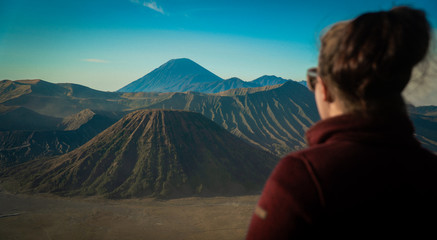 Back of Female's Head wearing trekking clothes and sunglasses, looking at Mount Bromo at Sunrise, Java, Indonesia
