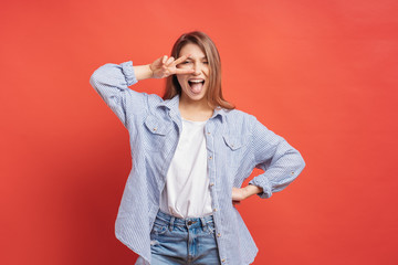 Funny, carefree girl having fun isolated on a red background with open mouth Papier Peint
