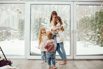 Beautiful mother with children. Family at home. People standing near winter windows