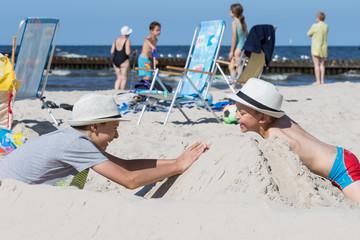Chłopcy bawiący się w piasku na plaży latem