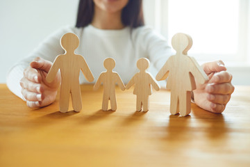 In the hands of a woman is a family of wooden figures. Family Planning Protection Concept