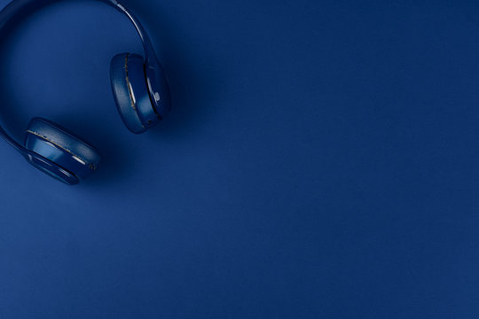 Blue headphones on blue background, top view