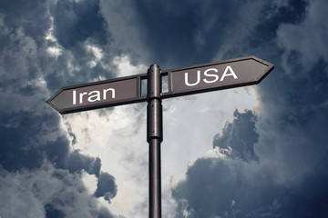 Road sign with the inscription Iran, USA against the backdrop of a stormy sky