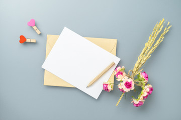 Mockup blank postcard and envelope on grey table background with craft rose flower. Mock up for...
