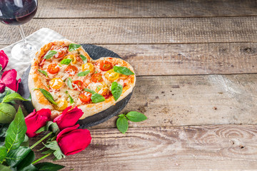 Pizza for Valentine day. Heart shaped homemade pizza margarita. Valentines day romantic menu concept. With wine bottle, roses flowers and and wineglass. Wooden background copy space
