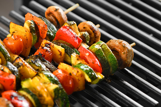 Barbecue vegetable skewers on a dark background from mushrooms, tomato, zucchini, pepper, buttery, bright, vegetarian. Dark background. Horizontally.