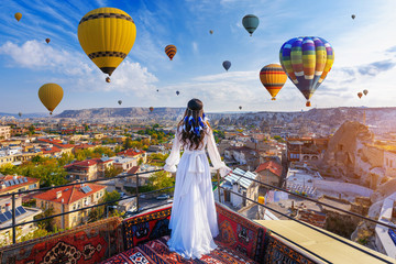 Beautiful girl standing on the hotel and looking to hot air balloons in Cappadocia, Turkey.