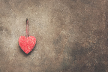 A red heart is hanging on a dark brown rustic wall. Valentine's Day. Copy space. Toned.