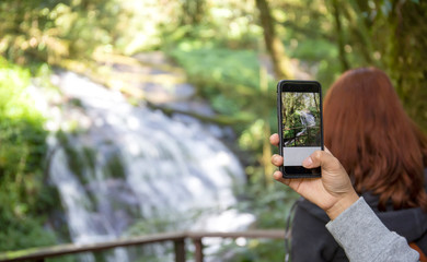 Women's hands using a tablet to take a photo of an exotic waterfall in a tropical rain forest.