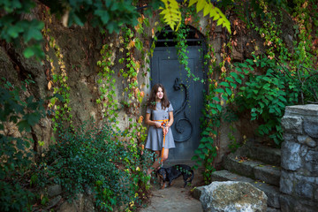 smiling  teen girl in dress with dachshund dog against  old metal door with  colorful  creeper plants around
