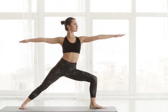 Fit girl making warrior yoga pose in light studio