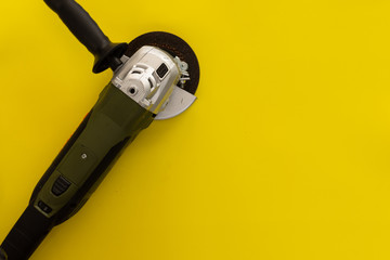 Angle Grinder over yellow background. Repair or construction tools concept.
