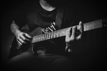 Close up view of man's hands playing electric guitar. Black and white picture