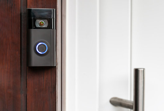 A modern surveillance camera is installed on a front door.A modern surveillance camera is installed on a front door.