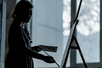 The silhouette of young girl artist is drawing the pictureon an easel against the window.  The figure of a girl with a brush, a concept of hobby and art.