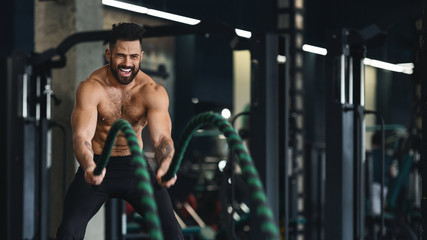 Wall Mural - Muscular bodybuilder training with battle rope at gym