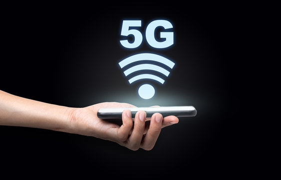 Hand of a business man holding a smartphone with 5 G wireless high speed Internet, Technology concept