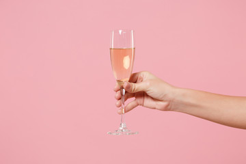 Close up cropped photo of female hold in hand glass of champagne isolated on pastel pink wall background. Copy space advertising mock up. Valentine's Day Women's Day birthday holiday party concept.