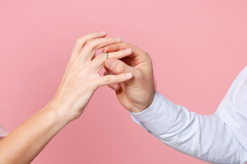 Close up cropped photo of female and male hold, putting proposal ring on finger isolated on pink...