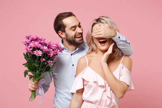 Cheerful young couple two guy girl in party outfit celebrating isolated on pastel pink background. Valentine's Day Women's Day birthday holiday concept. Hold bouquet of flowers, cover eyes with hand.