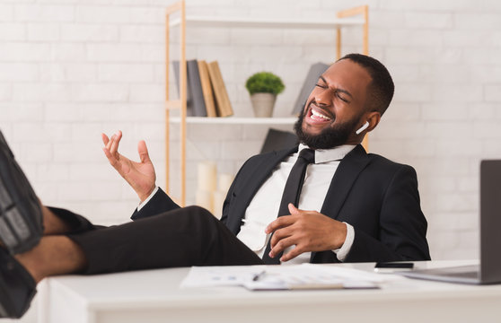 Emotional afro businessman listening to music at workplace
