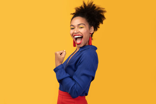 Happy afro woman triumphing with raised hands