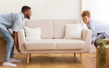 African American Spouses Lifting Heavy Couch In New Apartment