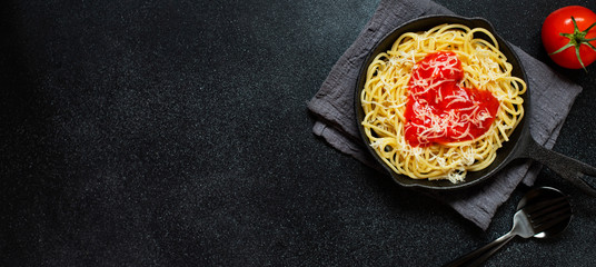 Spaghetti pasta with heart shaped tomato sauce, served in a pan. Dinner for Valentine's Day. Food with love. Top view, flat lay, black background