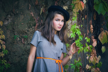 cute teen girl in dress and black beret retro style look outdoor near green and yellow creeper plant