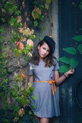 beautiful  teen girl in dress and black beret retro style look outdoor near old metal door and colorful creeper around