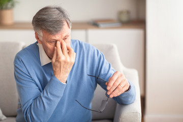 Senior Man Massaging Nosebridge Sitting On Sofa, Selective Focus